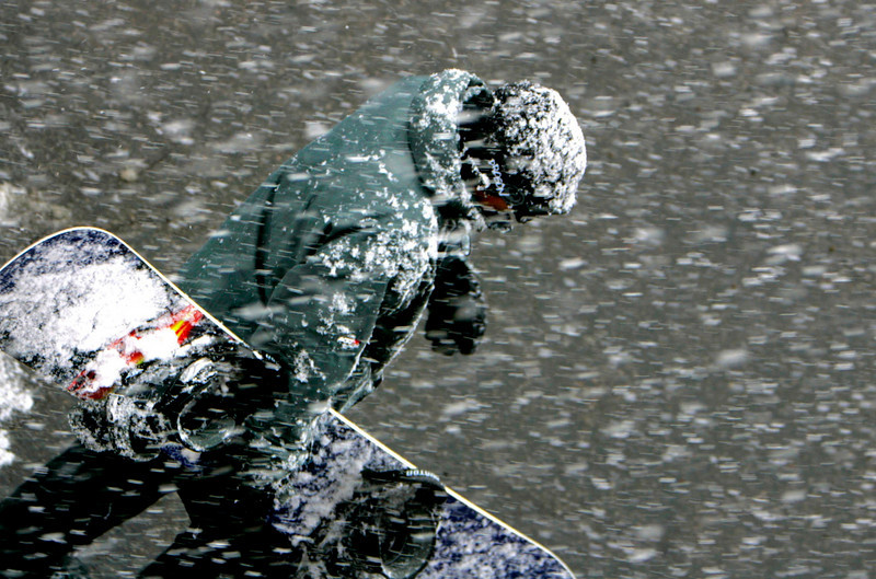 Flurry:   A snowboarder runs through the parking lot during a sudden snow flurry that hit  Bear Mountain Ski Resort in Big Bear.