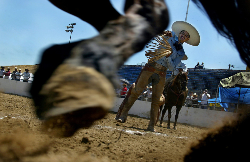 "Ramiro Gurrola competes at The Gran Charreada Mexican Rodeo held in Sacramento.  Each Charro (cowboy) was judged  based on skills, style and horsemanship.  Gurrola <br /> competes in the ""Las Manganas"", which consists of fancy rope twirling then roping the legs of a fast-running horse.  These fancy moves placed Gurrola in first place."