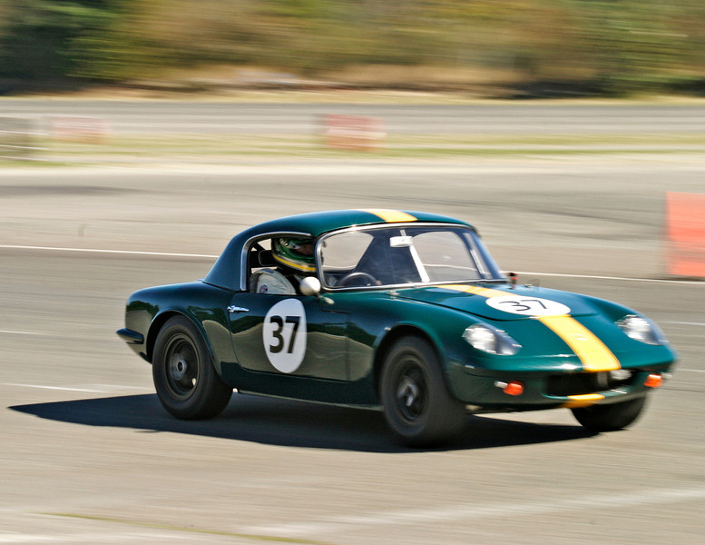 An old vintage green Lotus race car moving at high speed during a road race.