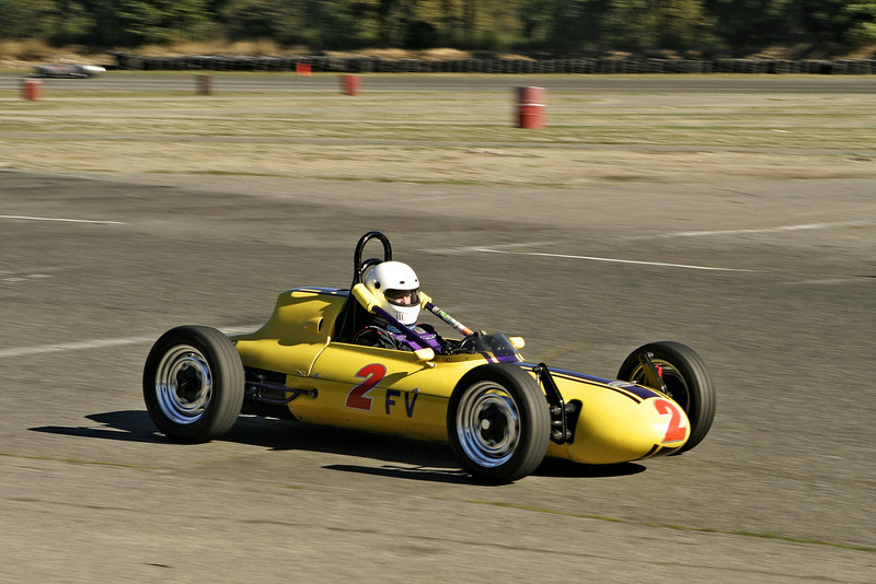A vintage yellow race car in a road race. As it was speeding around the track, the motion blur of the background is due to the speed.