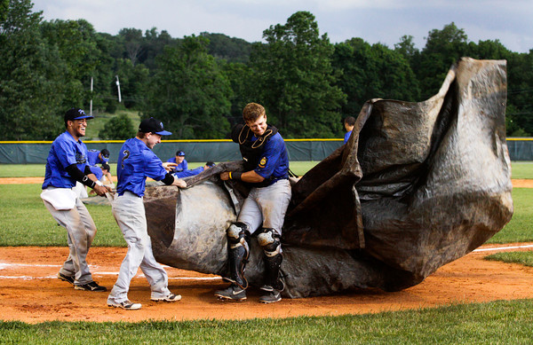 American Legion Post 42 players, from left, Nathaniel Jones, Josh Wenning, and Drew Kissell struggle with a tarp while trying to cover home plate during a rain delay in the second inning of their game against the Hoosier Express, out of Santa Claus, in Floyds Knobs on Tuesday. Staff photo by Christopher Fryer