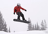 A snowboarder with a red coat getting big air in a jump. It was snowing heavily and the snowflakes are motion-blurred as I panned with the boarder.