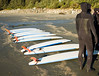 A row of surboards lined up on a beach in British Columbia while a group of neophyte surfers in wetsuits listens to instructions.