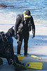 Two scuba divers preparing for a dive on a southern California beach. The divers are doing a last check on their equipment before going into the water.