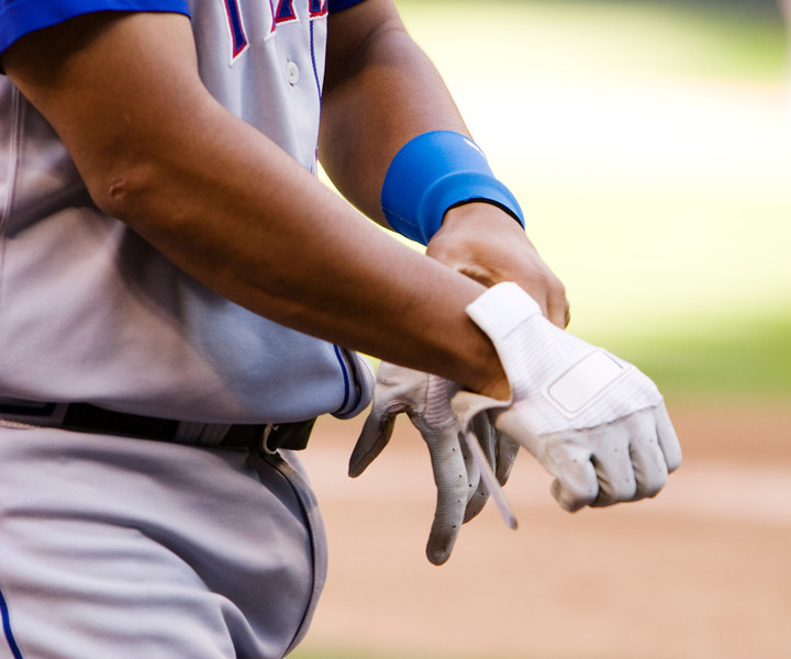 A baseball player putting on a pair of batting gloves while waiting his turn to go the the plate.