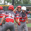 Goshen sophomore Nate Pinarski (2) celebrates with senior Colin Turner (24) after scoring on a sacrifice fly by Ezequiel Moreno (18) during Thursday's sectional game against Penn in Middlebury.