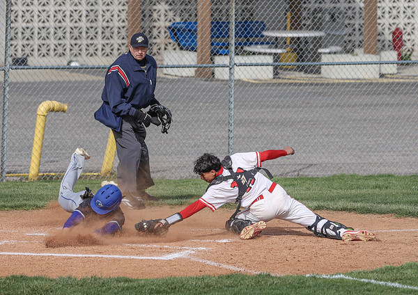 Goshen catcher Thomas Castillo tries to tag Elkhart's Graham Elli as he slides into home during Thursday night's game in Goshen.