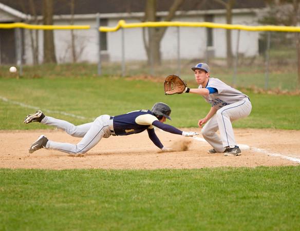 SAM HOUSEHOLDER | THE GOSHEN NEWS<br /> Mishawaka Marian first baseman Joe Ravatto looks to catch out Fairfield pitcher senior Andrew Bobeck during the game Friday.