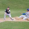SAM HOUSEHOLDER | THE GOSHEN NEWS<br /> Fairfield third baseman junior Sam Brown catches a ball as Mishawaka Marian outfielder Nate Thomas slides into third during the game.