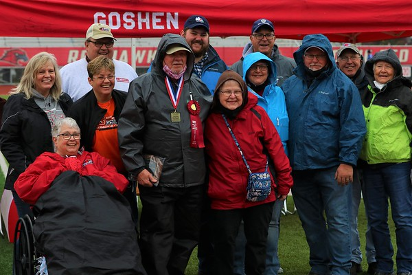 Larry Biller, pictured middle, poses with family during the Goshen Relays on Saturday at Goshen High School. Biller was named the honorary referee for the event.