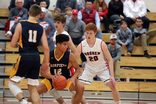 GREG KEIM   THE GOSHEN NEWS<br /> Junior Cordell Hofer of the Fairfield Falcons, No. 12, works the ball into position while being guarded by senior Brockton Yoder of the Goshen RedHawks in a high school boys basketball game Saturday night at Goshen.