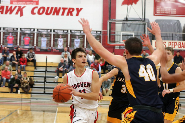 GREG KEIM | THE GOSHEN NEWS<br /> Senior Will Line of the Goshen RedHawks gets ready to put up a shot against the Fairfield Falcons in a high school boys basketball game Saturday night at Goshen. Defending on the play is Falcon senior Caleb Goeglein.