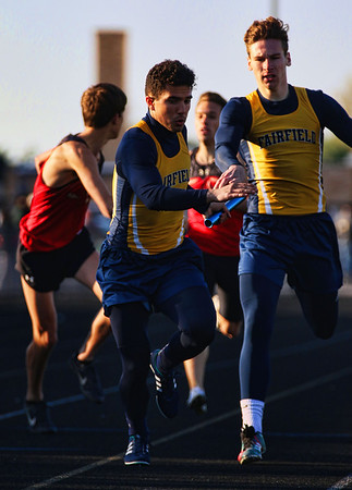 JAY YOUNG | THE GOSHEN NEWS<br /> Fairfield's Brady Willard, front, takes the baton from teammate Zac Lantz as they race in the 4x400 relay at the 47th annual Kelly Relays Friday evening at Concord High School.