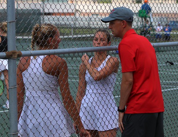 Goshen tennis coach Daniel Love, right, talks to senior Kathryn Detweiler, left, and senior Joya Drenth, center, during Detweiler and Drenth's match at the state individual doubles tournament Friday at North Central High School in Indianapolis. Detweiler and Drenth lost to Carmel's Alexa Lewis and Hallie Reeves, 6-1, 6-2.