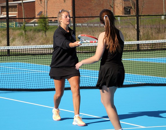 NorthWood's Amy Adams reaches out her racket to celebrate a point with teammate Emery Porter during their win at No. 2 doubles over Concord Friday in Elkhart.