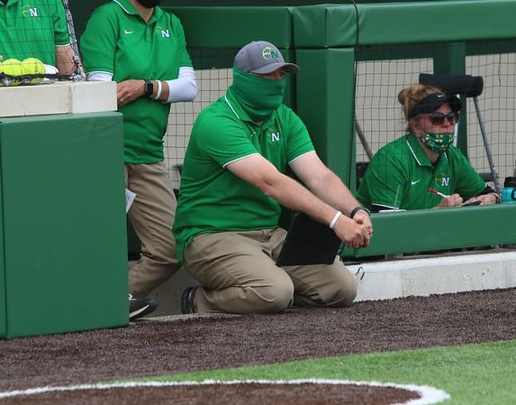 Northridge softball head coach Ray Caples, crouching, looks on during Monday's game against Mishawaka in Middlebury.
