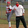 Goshen softball assistant coach Mike Barger, right, gives an elbow bump to sophomore Tyra Marcum after Marcum's RBI single in the first inning of Wednesday's game against South Bend Riley in Goshen.