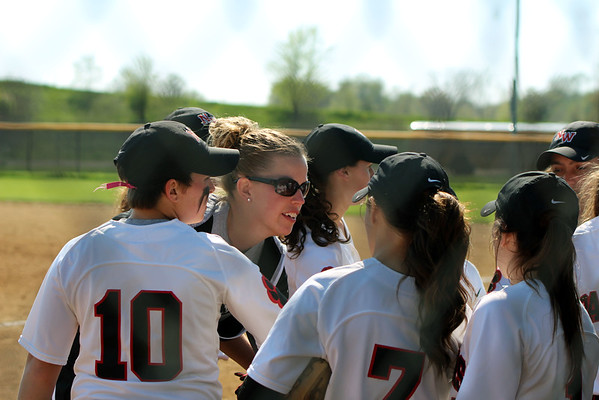 GREG KEIM | THE GOSHEN NEWS<br /> NorthWood coach Mandy DeMien (sunglasses) encourages her team between innings on an NLC softball game with Concord Thursday night at Stauffer Park in Nappanee.