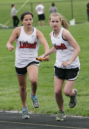 Kate Thurston/Rushville Republican<br /> Rushville's Kayla Fogg hands the baton to Monica Dougherty in the 3200-meter relay event Tuesday.
