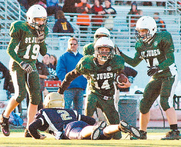 St. Jude's Jack Klingshirn (14) is congratulated by Grant Williams (19) and Will Lacinak after an interception late in Sunday's Division I CYO Cleveland Diocese championship game against Gesu at Bedford Stadium. St. Jude's won 14-12 in overtime to finish the season 9-0-1 and claim the title in head coach Brian Hoagland's final season.