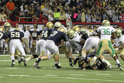 Buford defensive lineman Brandon Brinson (#90) meets St. Pius X High School fullback Ryan Braswell (#3) at the line of scrimmage.