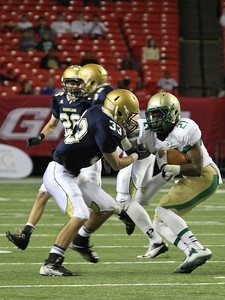 St. Pius defensive back Brian O'Reilly (#33) moves in to bring down Buford running back Thomas Wilson (#21).