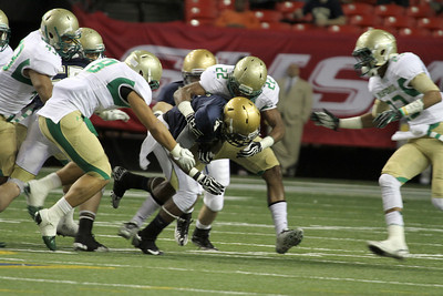 St. Pius running back Branden Mitchell (#4) is tackled and brought down by Buford linebacker Bryson Jordan (#22).