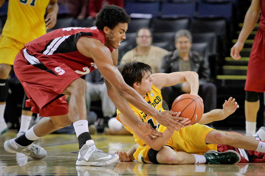 Josh Huestis (24) of Stanford tries to wrestle the ball from Cody Doolin (45) of USF  in Men's Basketball at the Oracle Arena in Oakland, Calif., on Friday, November 9th, 2012