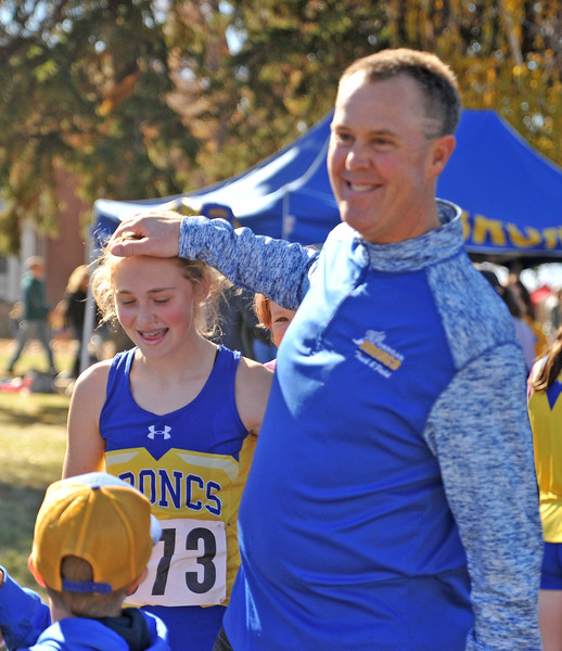 Ryan Patterson | The Sheridan Press<br /> Sheridan head coach Art Baures, right, congratulates Katie Turpin after her race during the state cross-country meet at the Veteran Affairs Medical Center in Sheridan on Saturday, Oct. 20, 2018. The Lady Broncs placed fifth as a team in the 4A race.