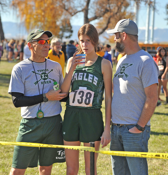 Ryan Patterson | The Sheridan Press<br /> Tongue River's Macey McArthur, center, recovers after her race with the support of head coach Tim Maze, left, during the state cross-country meet at the Veteran Affairs Medical Center in Sheridan on Saturday, Oct. 20, 2018. The Lady Eagles took fifth as a team in the 2A race.