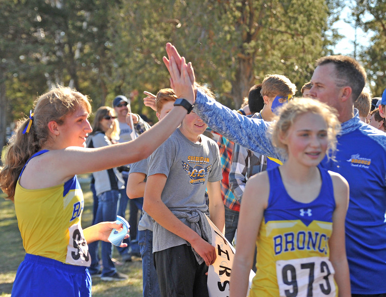 Ryan Patterson | The Sheridan Press<br /> Sheridan's Sarah Gonda, left, high-fives head coach Art Baures after her race during the state cross-country meet at the Veteran Affairs Medical Center in Sheridan on Saturday, Oct. 20, 2018. The Lady Broncs took fifth as a team in the 4A race.