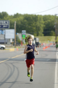 Aaron Schaffer-Neitz strides home comfortably as he crossed the finish line in first place overall at Saturday's Sunbury YMCA 5k race.