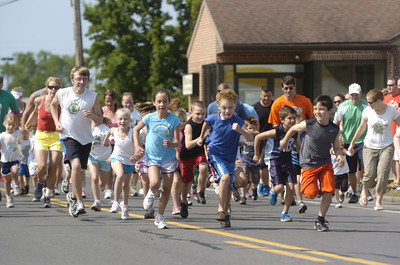 Kids and some parents take off at the start of the kids fun run on Saturday after the Sunbury YMCA's 5k race.