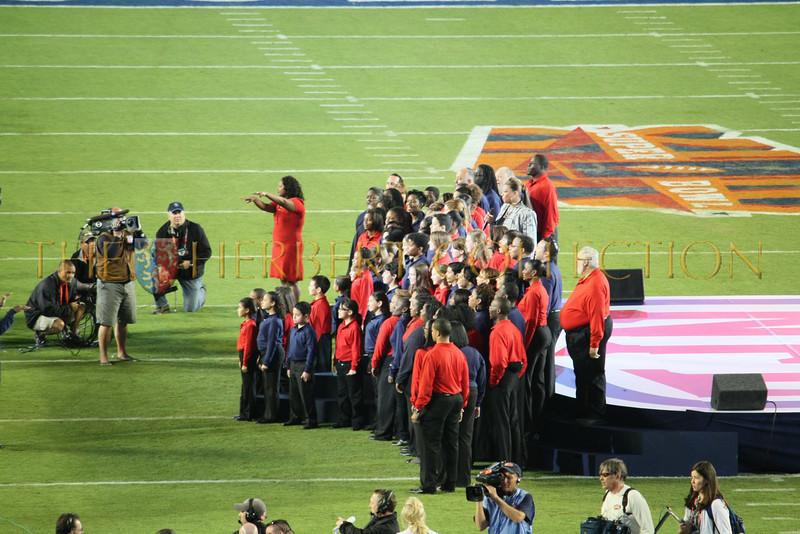 Queen Latifah sings National Anthem (in grey, back row)
