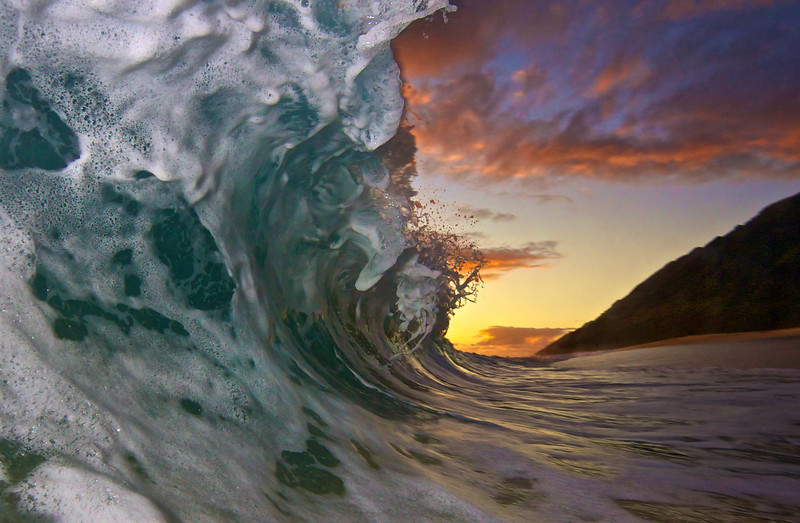 Warm sunset with a wave crashing on a secret beach.