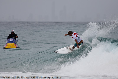 The high-rise buildings of Surfers Paradise and Broadbeach are barely visible as this surfer completes his run - Quiksilver Pro, Snapper Rocks, 27 February 2010.