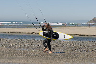 wind surfer walking his kit to the beach.  Cardiff, California.