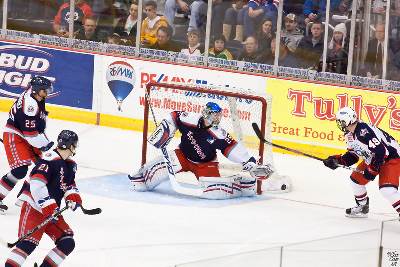 Hartford goalie Chad Johnson makes a save,as Syracuse's Dan Fritsche looks for the rebound.