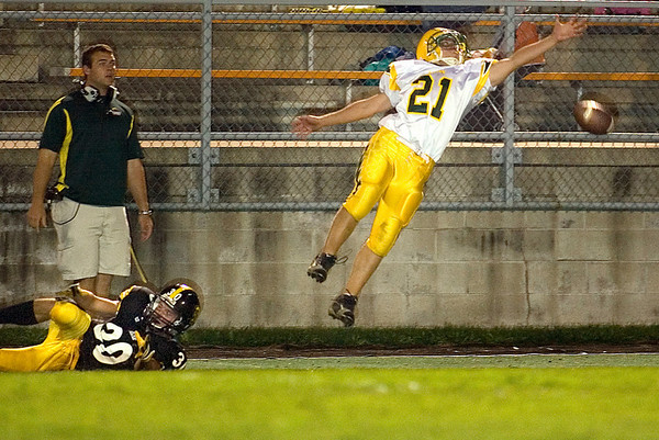 Record-Eagle/Jan-Michael Stump<br /> Midland Dow's Philip Bunge (21) reaches for a pass to Traverse City Central's Dylan Roe (30) in the third quarter of Friday's game.