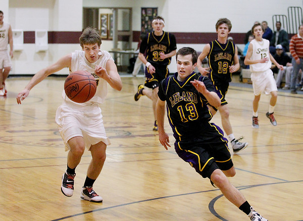 Record-Eagle/Keith King<br /> Traverse City Christian's Andrew Bump, left, and Leland's Dylan Jolliffe hustle to obtain possession of the ball Monday, February 13, 2012 at Traverse City Christian School.