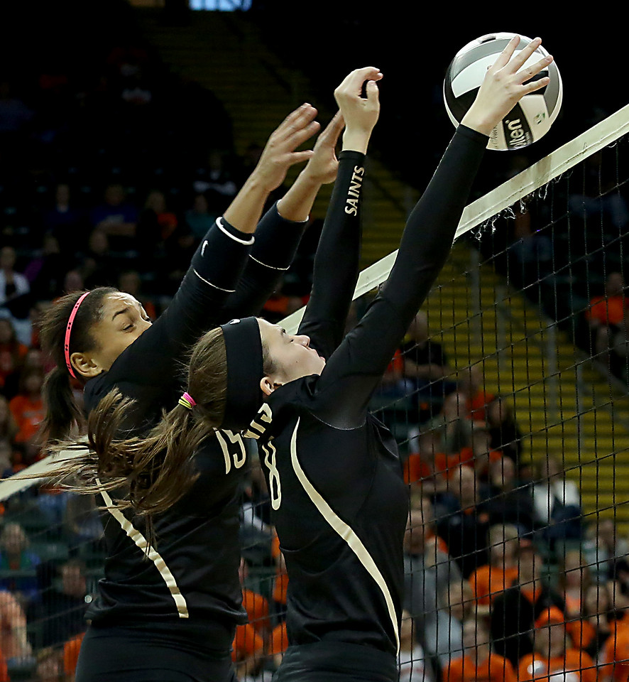 E.L. Hubbard / Special to GateHouse Ohio Media<br /> New Philadelphia Tuscarawas Central Catholic's Maggie Dominick and Molly Triplett stop a Jackson Center volley during their Division IV State Championship game at Wright State's Nutter Center in Fairborn Saturday, Nov. 12, 2016.