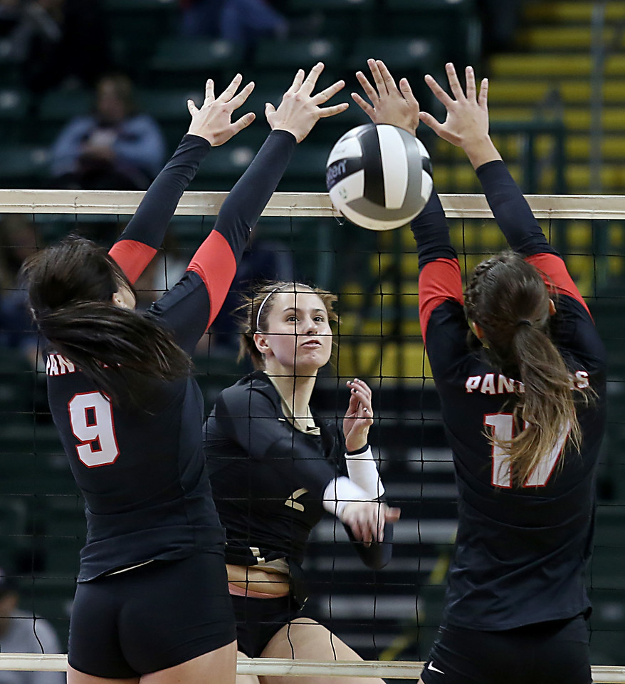 E.L. Hubbard / Special to GateHouse Ohio Media<br /> New Philadelphia Tuscarawas Central Catholic S/OH Sydney Gilland spikes the ball past McComb's MaKenna Babb and Alysha Like during their Division IV semifinal at Wright State's Nutter Center in Fairborn Friday, Nov. 11, 2016.