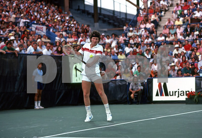 A packed stadium watches John McEnroe hit a backhand vs Bjorn Borg at the US Open in 1981, Flushing Meadows, NY.