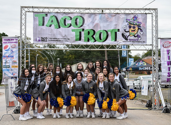 The Jacksonville High School cheerleaders gathered for a photo underneath the finish line of the Taco Trot 5K on Saturday.