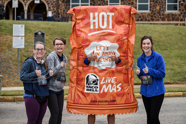 Sisters (from left) Ali Carnes, Abi Carnes and Chloe Carnes smile for a photo with the Taco Bell hot sauce prior to running the Taco Trot on Saturday. The event took place in downtown Jacksonville and benefitted the American Cancer Society.