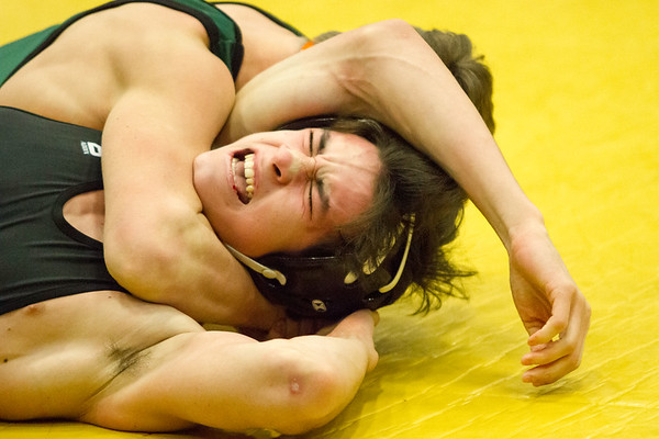 Record-Eagle/Brett A. Sommers Traverse City Central's Isaac Battle tries to fight off the impending pin of Traverse City West's Wylie Edick during Wednesday's team district wrestling meet at Central High School. West defeated Central 43-29 and Alpena 51-19 to win its third straight district title.