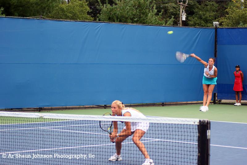Alona Bondarenko at net and sister Kateryna Bondarenko serving
