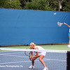 Alona Bondarenko at net and sister Kateryna Bondarenko serving