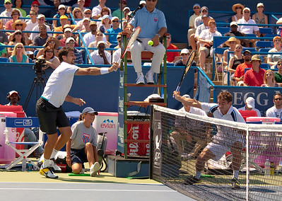 Tommy Robredo defends against smash by Nenad Zimonjić in a doubles match