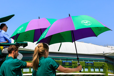 Wimbledon court attendants holding umbrellas above players for shade, All England Lawn Tennis Club Wimbledon, UK